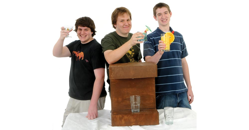 From left to right: Nick Pegg, Richard Allen and Jon Blount stand behind their wooden drink dispenser that's sitting on a table.