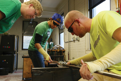 Austin Gerlt, a senior in ceramic engineering (left), and Martin Langenderfer, a senior in mining engineering (right), work together in the shop to create an open container with clear glass.