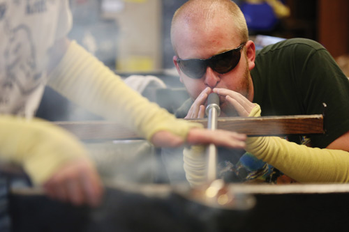 A senior in mining engineering, Martin Langenderfer carefully blows into the pipe as it rolls across the bench to keep the glass symmetrical when manipulated with a shaping tool.