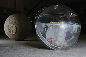 In the foreground, a passive smart rock contains a magnet suspended in liquid. In the background is a concrete-encased smart rock that is about the size of a basketball and weighs about 50 lbs.