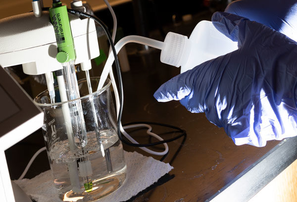 Photo of adding CO2 to Lime Water solution to create CO2- ions and HCO3- ions. And then testing with a Ph meter probe