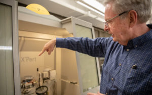 Jay Switzer stands to the right of the spin coating machine explaining the process used to produce epitaxial films and nanocrystals.