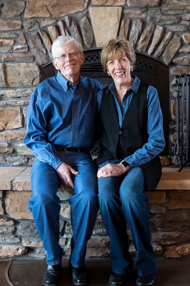 Joan Woodard sits to the right of her husband in front of the stone fireplace in their home.