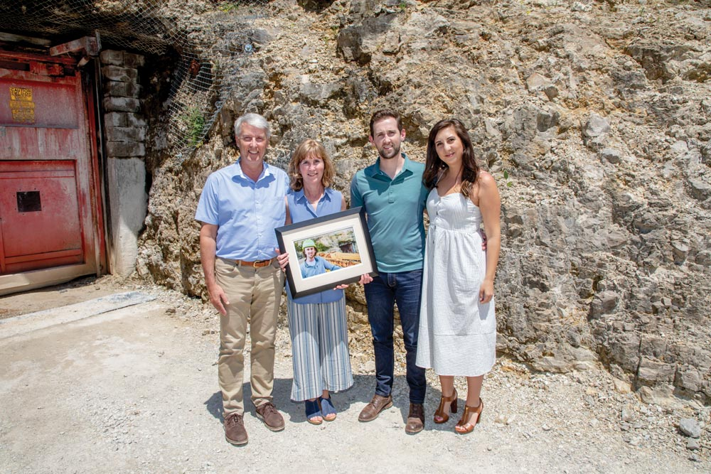 Beasley family stands infront of the Missouri S&T mine holding a picture of their son Patrick.