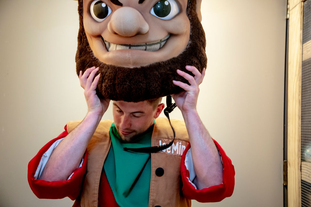 Travis Gittemeier puts on the head of his Joe Miner mascot uniform.