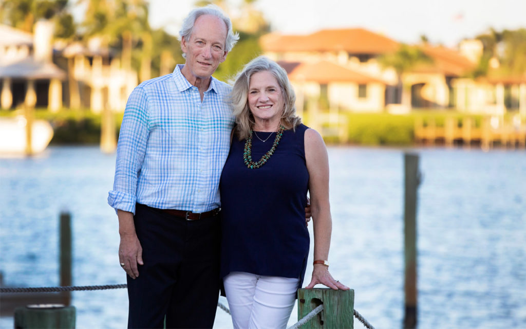 Mike and Linda Evans stand together on a dock.