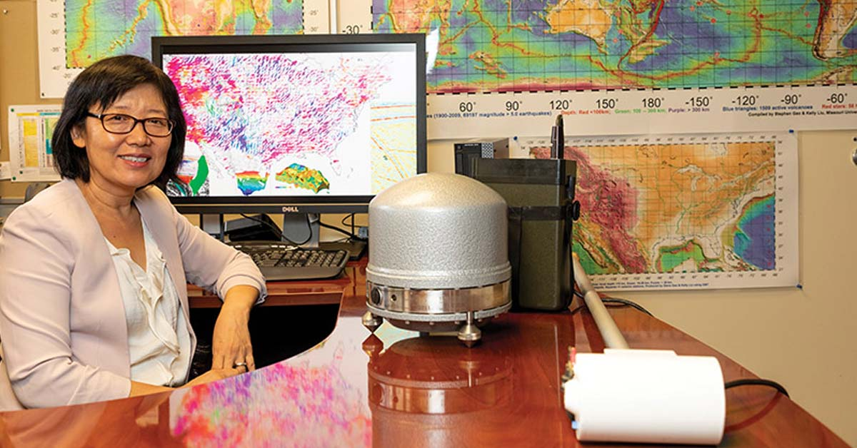 Portrait of Dr. Kelly Liu, professor Geosciences & Geological & Petro Engineering, photographed in her office, with information on her computer screen and on the wall relating to her research around the world working to predict earthquakes.