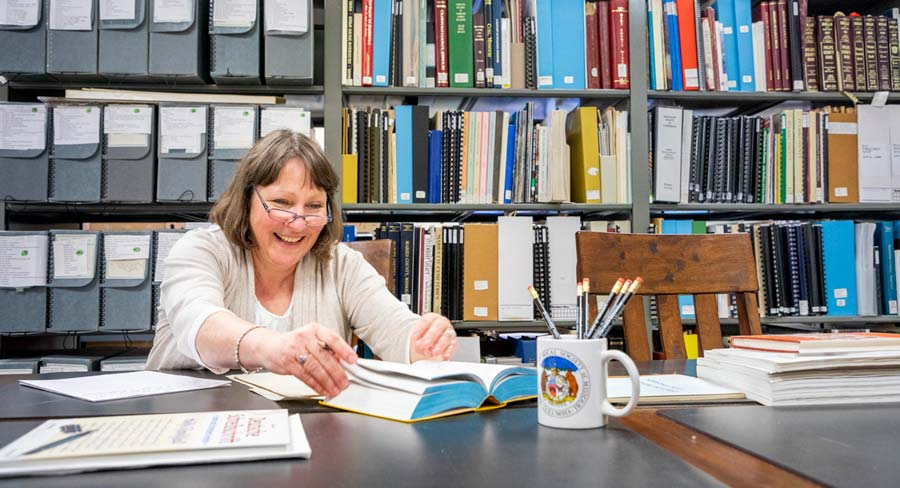Petra DeWitt sits at a table with shelves of artifacts and historical documents behind her. She's in the Missouri State archive looking through a book about Missouri's German hertiage.